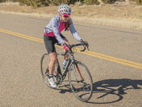 Woman cyclist riding on the road while wearing the Divide Wind Jacket