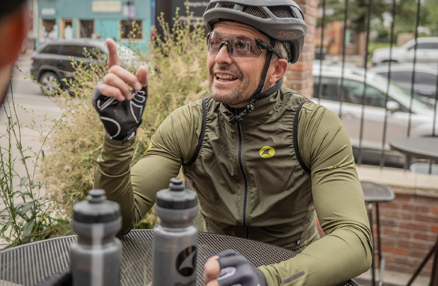 Male cyclist wearing long sleeve green cycling jersey and vest at coffee shop