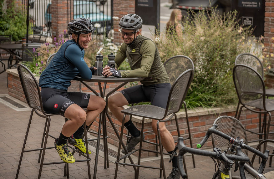 Male and female cyclists wearing long sleeve cycling jerseys at coffee shop