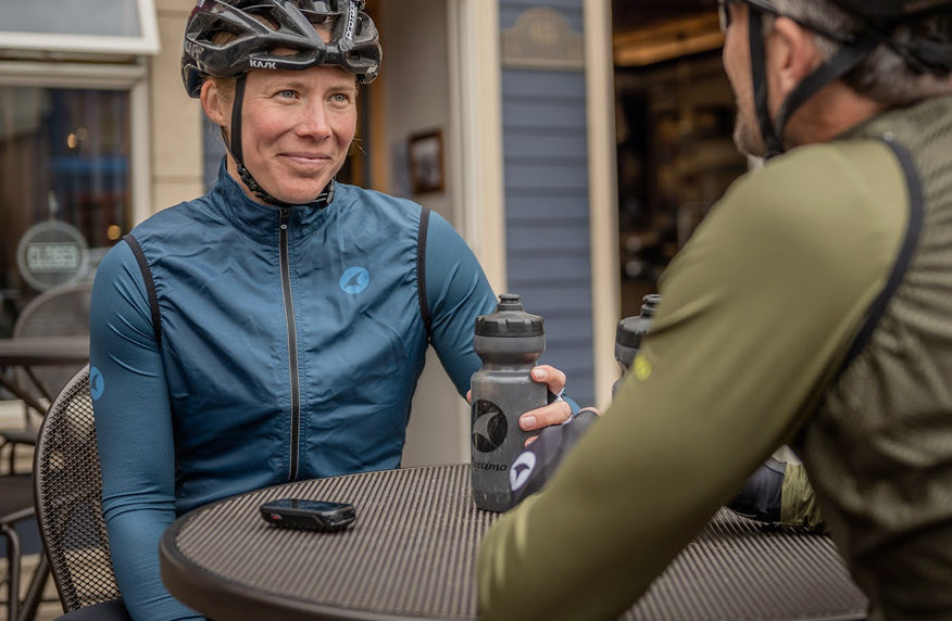Female cyclist wearing blue jersey and vest at coffee shop