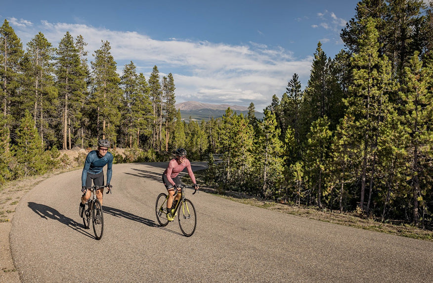 Male and female cyclist riding on road with mountains in the distance