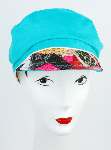 100% organic cotton blue cap has a multi fabric peak. Detailed with Ivory piping on band of cap.