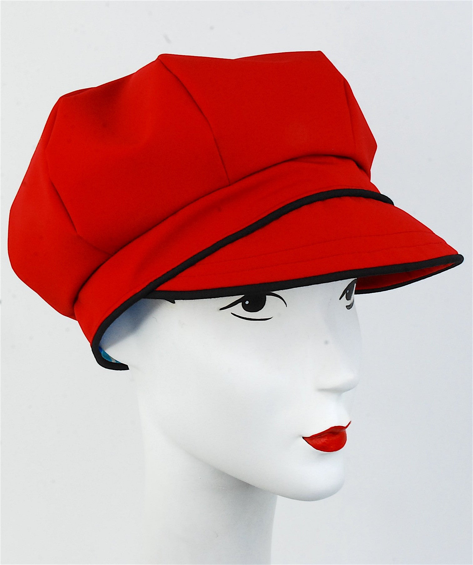 This darling waterproof and breathable fabric is amazing! Lightweight and perfect for stepping out in drizzly weather. Packs well in a bag and you can just throw it one when you need some protection from the weather. The cap is a darker red color, not an orange tone at all. Will compliment many skin tones. This hat is made to order in your head size.