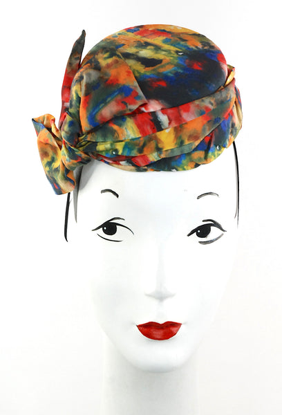 This stunning Jackie O styled pillbox is made out of lovely 100% print silk with bow detail.  It is one of a kind and attaches with a hat elastic. All handmade with attention to detail.