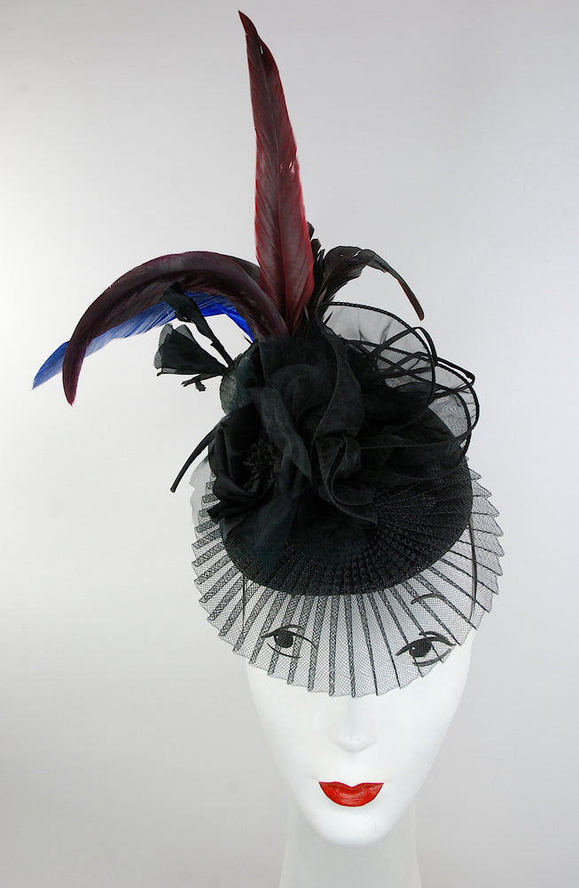 This unique headpiece is made with red and blue feathers ( these are natural and have their own imperfections). The hat is detailed with silk flowers and sheer fabric swirled around. Hat attached with hat elastic. Perfect for the races or any occasion.