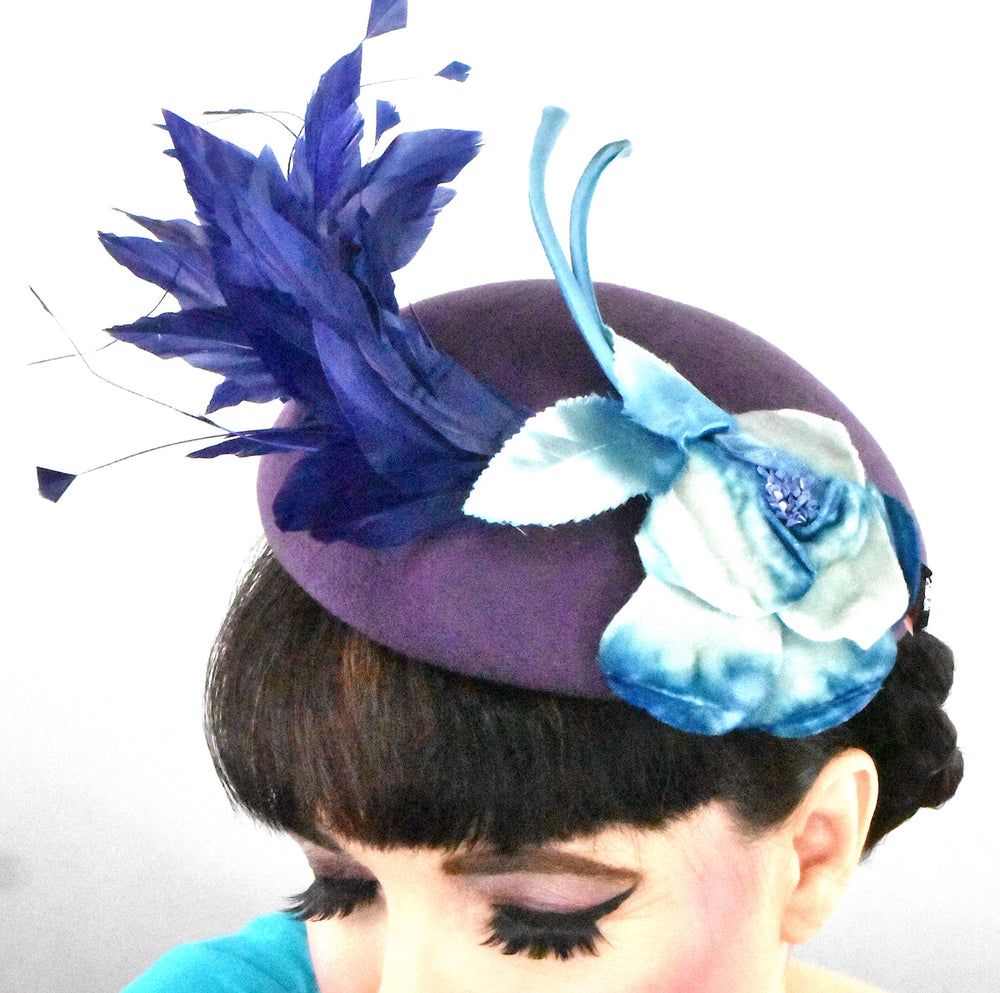 this purple wool blocked beret is adorned with a blue vintage velvet flower