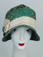 This original green and  gold embroidered satin cloche hat is made with an  ivory silk band and detail. It sits lower over the ears with a smaller more elegant brim. The brim detail is a  complimentary green wool.