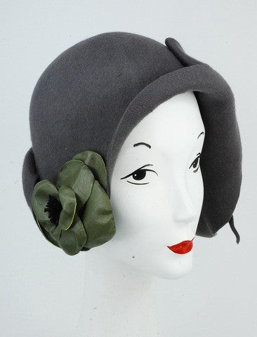 This original grey 100% fur felt cloche hat is hand blocked with a green hand made leather flower. This hat has a unique shape and look to it, cloche inspired design. The design is free style blocking method.