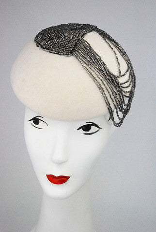 IAn original design ,this Ivory wool blocked beret is adorned with stunning beading. It is 100% wool and Attaches with hat elastic or clips.