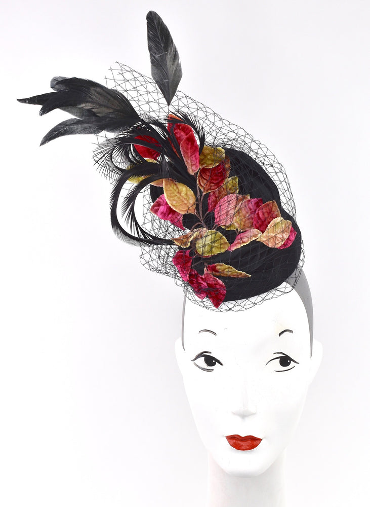 This  chic headpiece is a made of black wool , netting ,feathers and vintage velvet leaves.  Attaches with hat elastic.