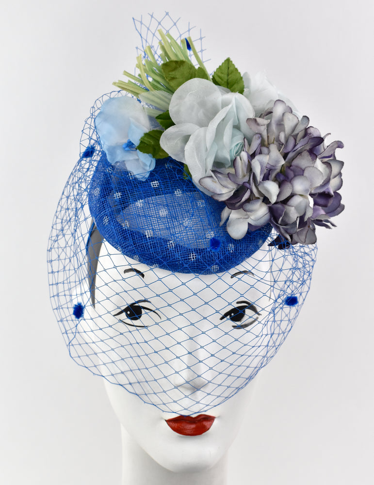 Blue spotted sinamay straw with various flowers and blue netting