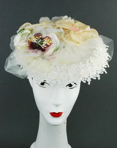 Lace, sinamay base and flowers made with tulle, imported lace and silk flowers. Attaches with hat elastic.