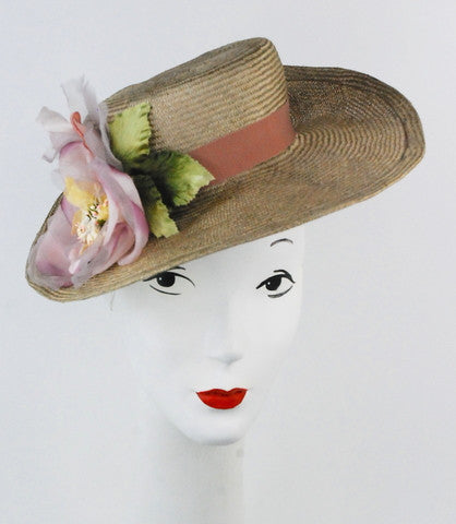 This hat is truly stunning on! It is a Parisisal  hand blocked  straw boater with large silk flower. It will fit most head sizes, attaches with elastic