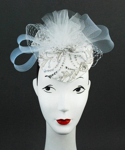 This lovely headpiece is detailed with white veiling, horsehair ribbon  and tulle with an embroidered  satin base. Stunning on! Base is 6 inches. Attaches with clip.