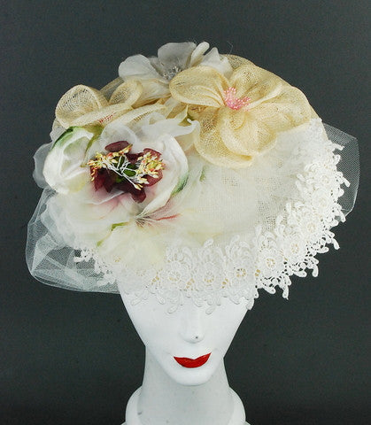 Lace, sinamay base and flowers made with tulle, imported lace and silk flowers. Attaches with hat elastic
