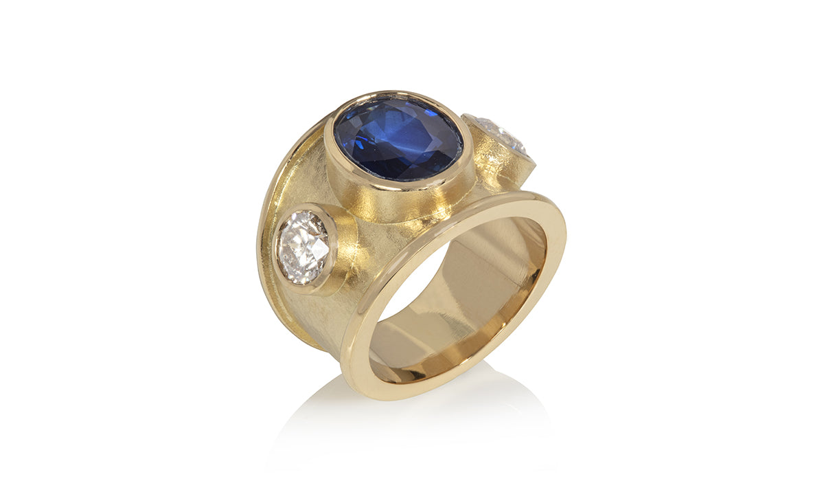 Wide yellow gold ring set with large oval sapphire and two round diamonds, bespoke commission