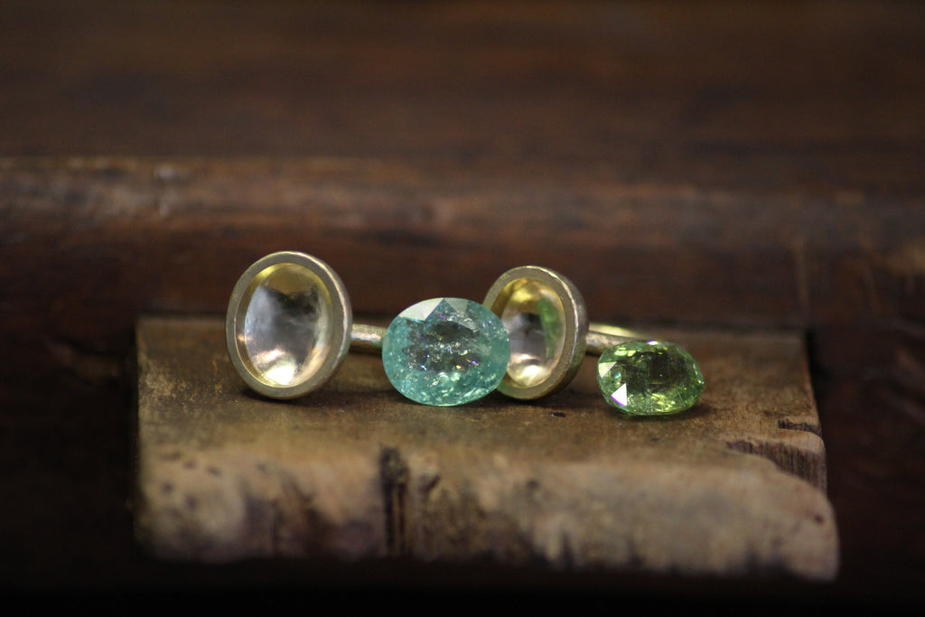 Paraiba tourmaline rings on the workbench, about to be set in Julia Lloyd George London studio