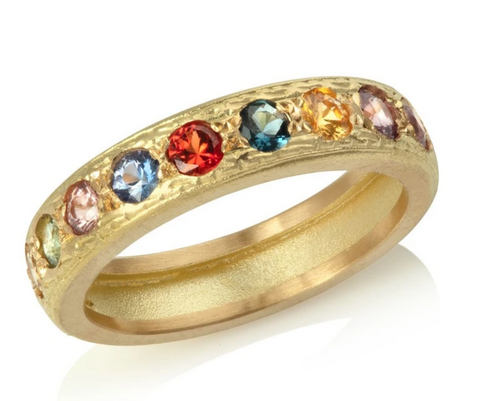 Yellow gold eternity ring set with fancy sapphires of an assortment of colours with engraved pattern detail