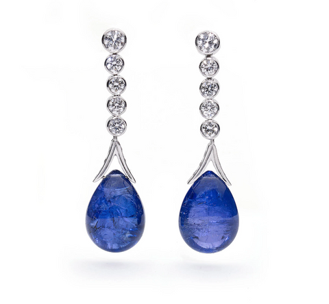 Statement white gold drop earrings set with round cut brilliant diamonds, with large pear shaped tanzanite cabochon drops