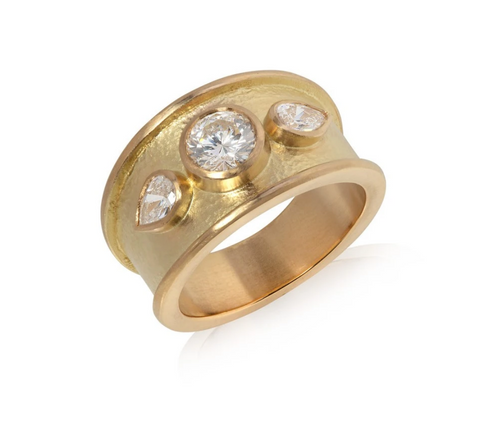 Large yellow gold ring set with one brilliant cut diamond and two pear shaped diamonds either side
