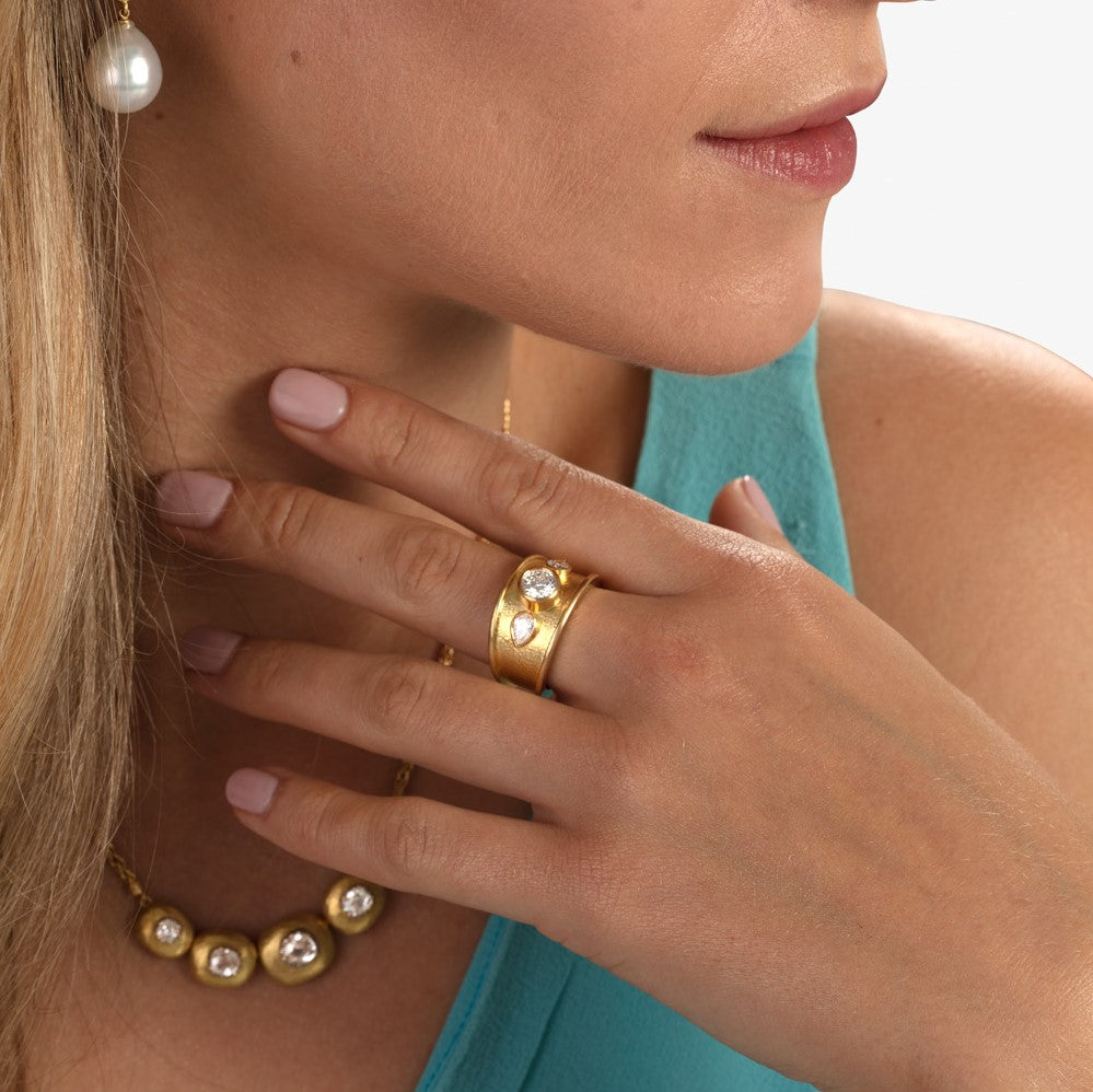 Model wearing thick yellow gold diamond ring