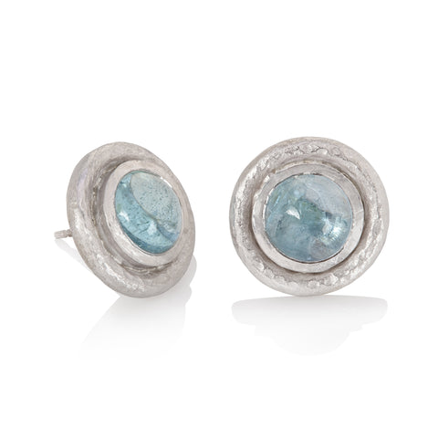 White gold stud earrings set with round aquamarine cabochon, finished with hammered texture