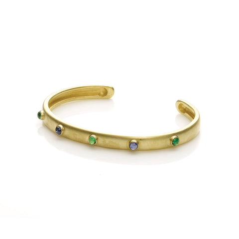 Oval yellow gold slip on bangle set with emeralds and sapphire cabochons