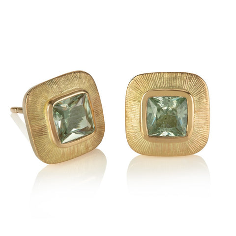 Stud earrings with cushion shaped pale green sapphires in wide yellow gold engraved borders