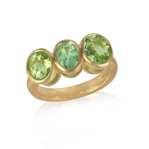 Yellow gold ring with three bezel set oval Paraiba tourmalines, of varied green tones