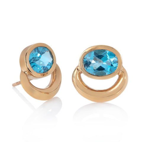 Yellow gold bull ring stud earrings set with oval blue topaz