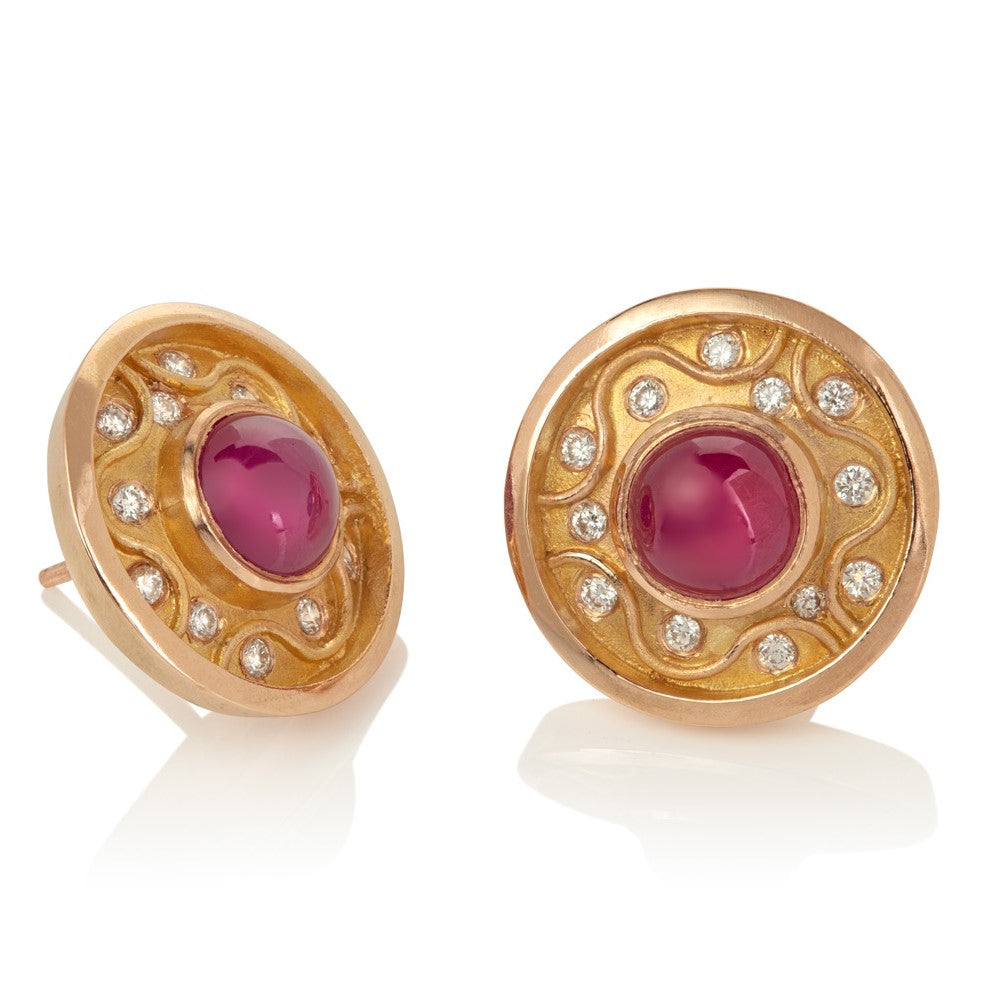Round stud earrings with central ruby cabochon surrounded by raised zigzag pattern with diamonds