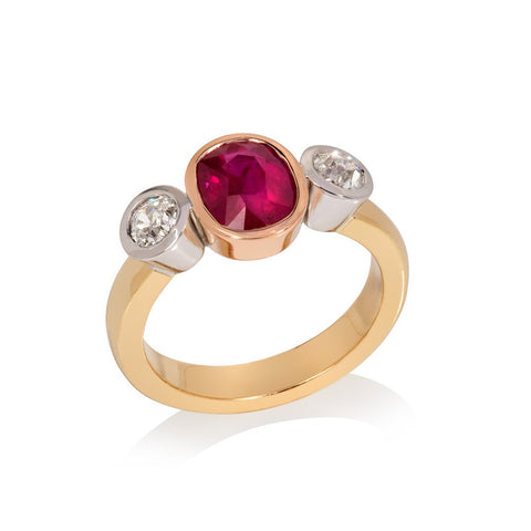 Central ruby set in red gold with two round cut diamonds set in white gold