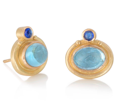 Stud earrings in yellow gold set with large oval aquamarine cabochons, with small round blue sapphires above
