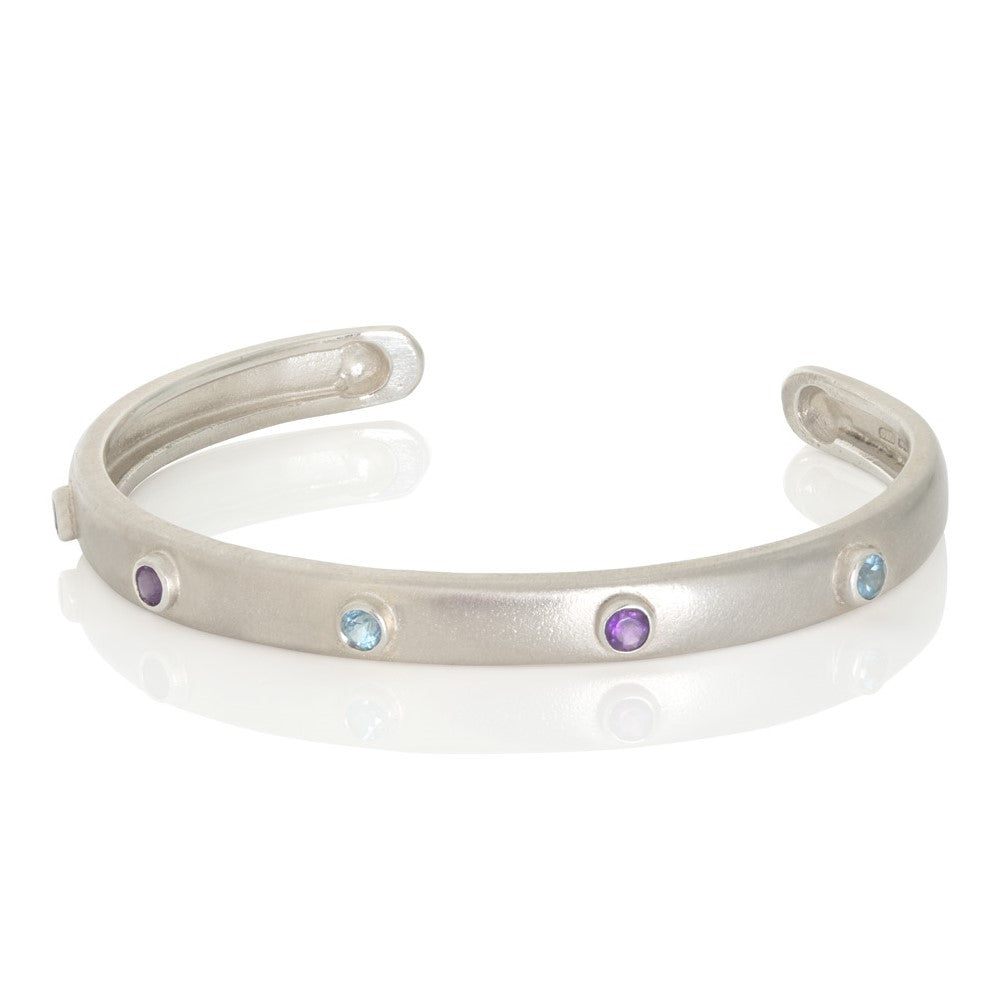 Silver bangle with blue topaz and amethyst on white background