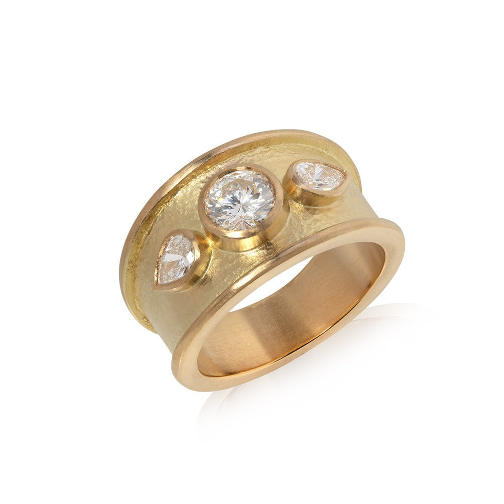Wide yellow gold ring with thick border set with round cut diamond with two pear shaped diamonds, hammered texture finish