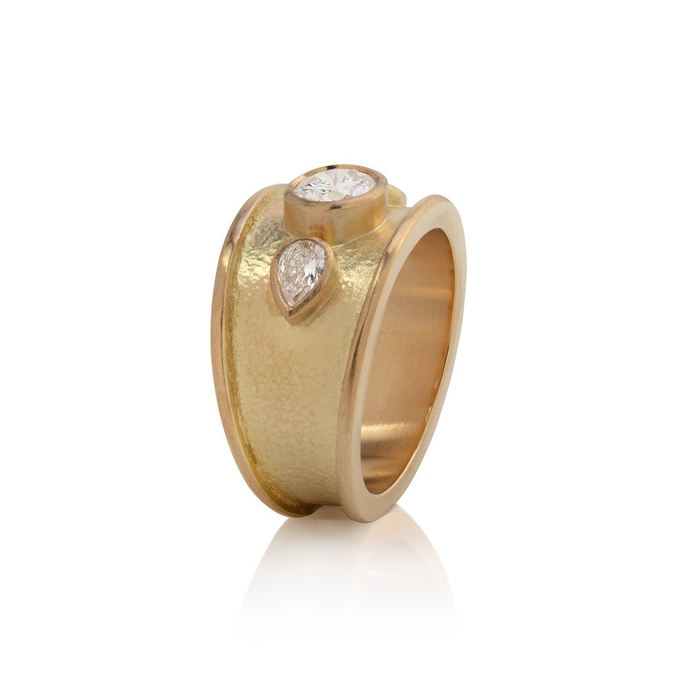 Wide yellow gold ring with thick border set with round cut diamond with two pear shaped diamonds, hammered texture finish, side view