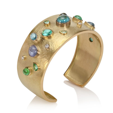 18ct yellow gold cuff bangle set with paraiba tourmalines and diamonds on a white background