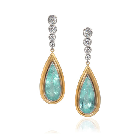 pear shaped Paraiba tourmalines set in yellow gold, hang below four round cut diamonds in decreasing size set in white gold