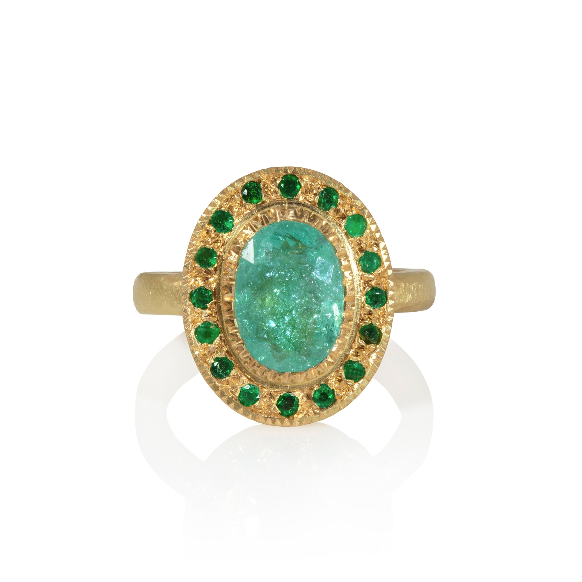 Head on view of Paraiba tourmaline and emerald ring on white background