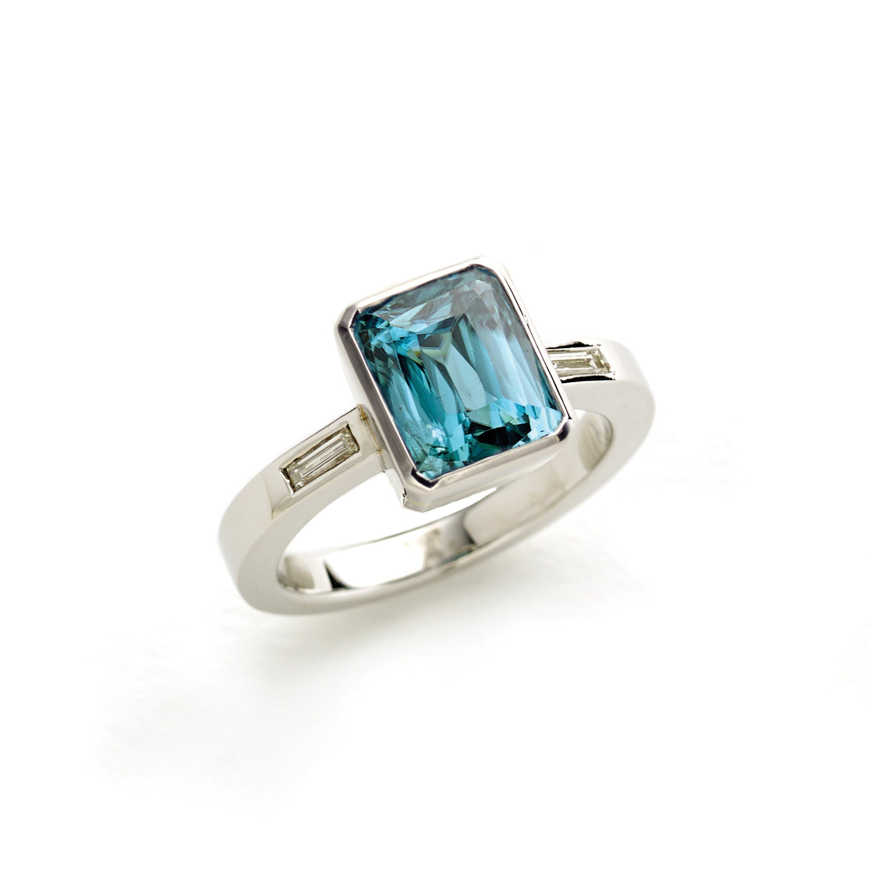 White gold ring set with blue zircon, with baguette diamonds set in shoulders of shank