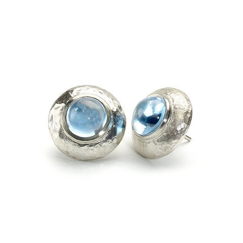 Stud earrings with round blue topaz cabochons set in hammered texture silver borders