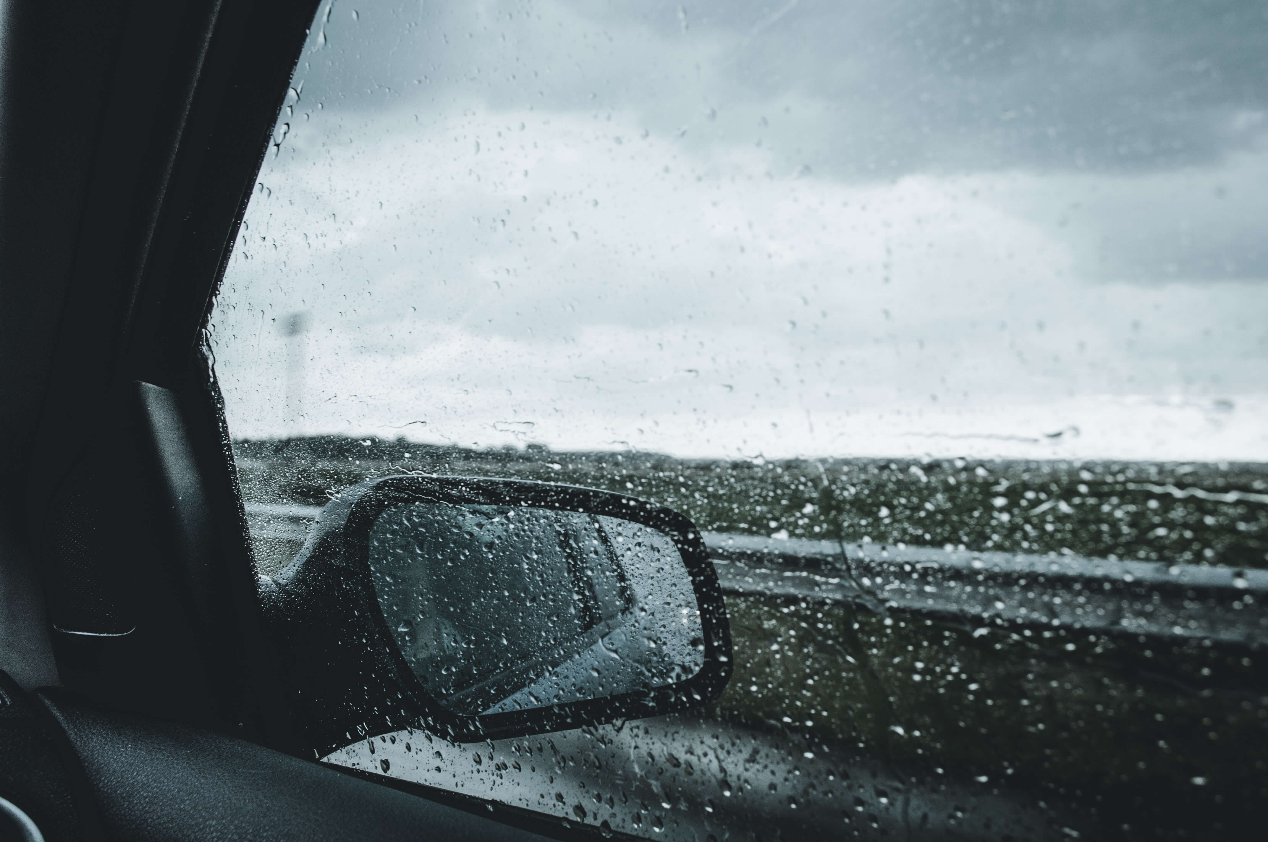 car wing mirror with rain on windows