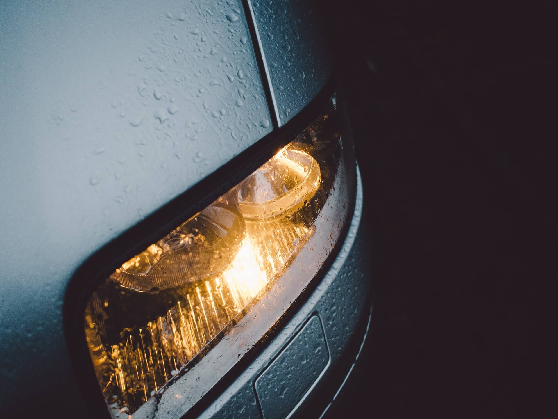 car headlight with yellow light and rain