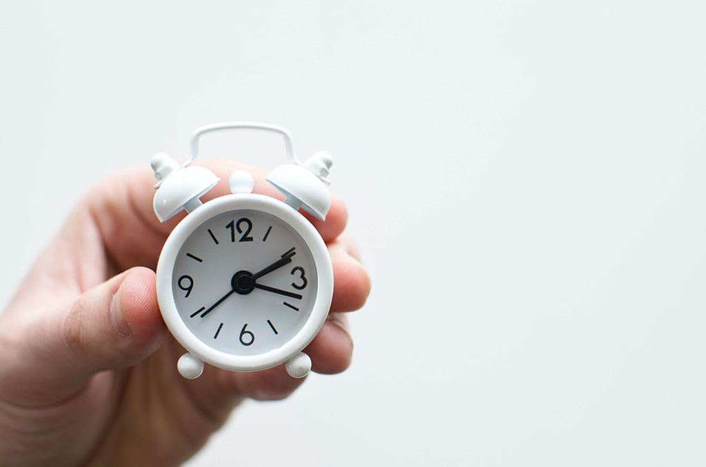 hand holding a small white alarm clock