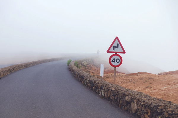 Road with fog and 40 miles per hour sign and tight bend warning