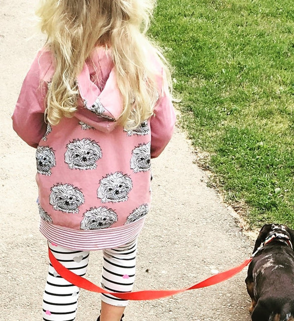 girl walking dog wearing pink puppy print hoodie