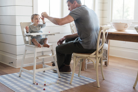 image of dad feeding baby in highchair