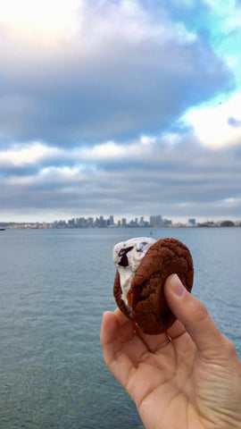 Enjoying ice cream cookie sandwich by water