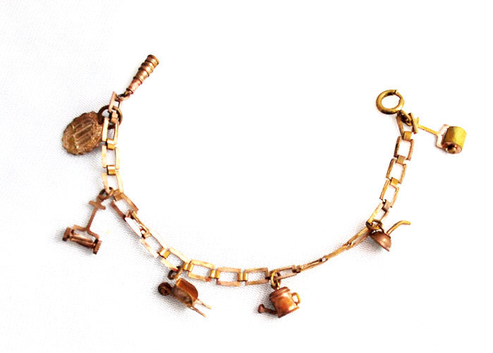 Splendid mid century copper charm bracelet with a gardening theme.