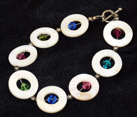 Multi-colored Swarovski crystals bring color and life to the creamy mother of pearl shell rings.